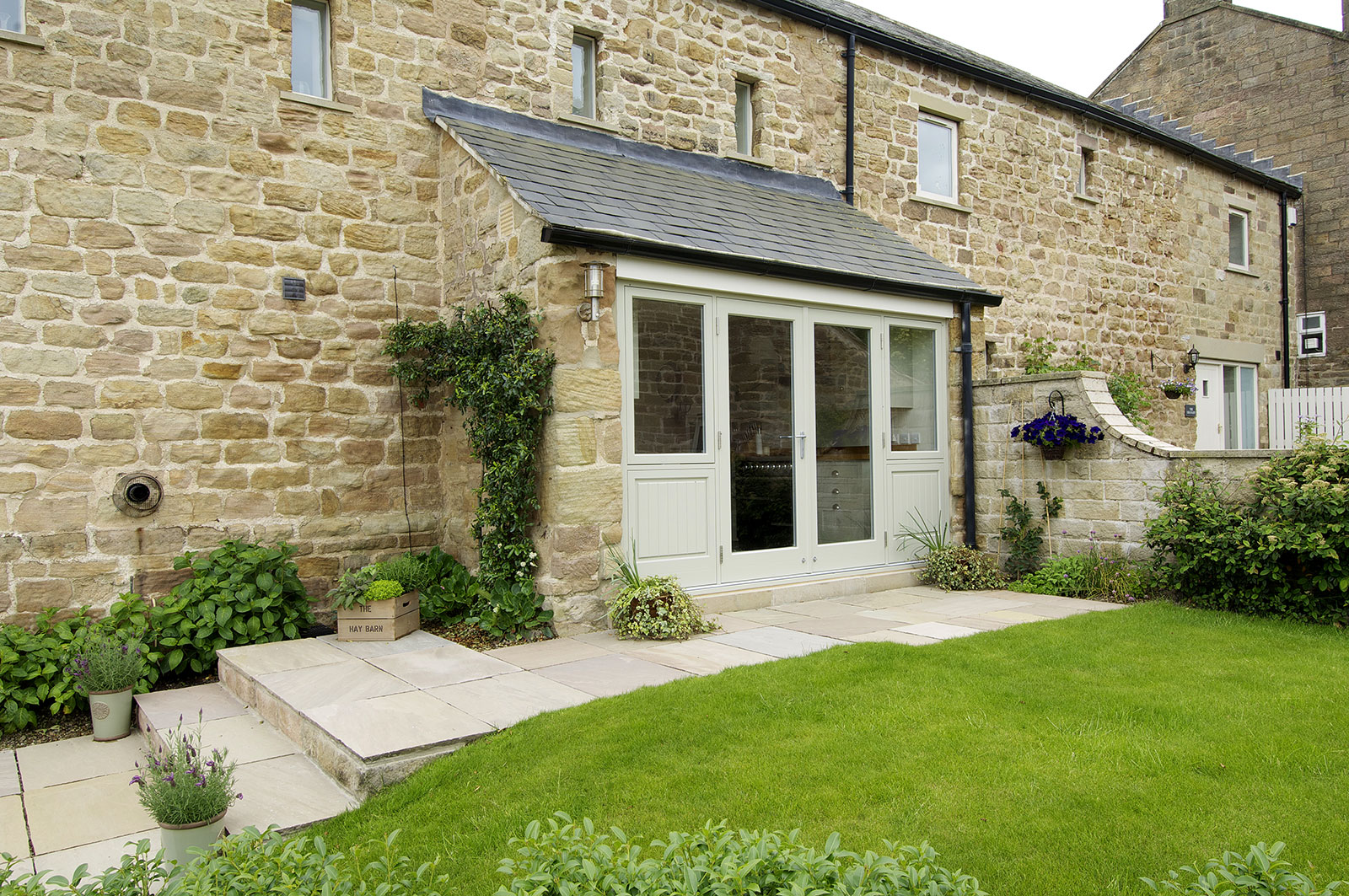 barn conversion with sage green wooden double doors